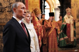Russian President Vladimir Putin, left, and his wife Lyudmila attend a service in the Annunciation Cathedral after his inauguration. (AP)