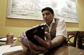 Bigyan Bhandari, a 28-year-old Nepalese who works at a Nepalese restaurant run by K.P. Sitoula, uses his smartphone to call his family members in Kathmandu during an interview in Seoul, South Korea, April 27, 2015.