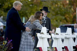 First lady Melania Trump, accompanied by President Donald Trump, and Tree of Life Rabbi Jeffrey Myers, right, puts down a white flower at a memorial for those killed at the Tree of Life Synagogue in Pittsburgh, Oct. 30, 2018.