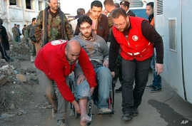 In this photo taken on Feb. 9, 2014, and released by the Syrian official news agency SANA, Syrian Arab Red Crescent members in red uniforms help evacuate an injured man on a bus out of the battleground city of Homs.