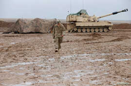 [÷/ُ - A U.S. soldier walks in front of a tank at an army base in Karamless town, east of Mosul, Iraq, December 25, 2016. Picture taken December 25, 2016.