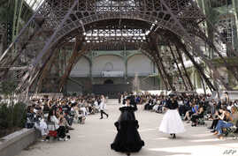 Models present creations for Chanel under a replica of the Eiffel Tower at the Grand Palais during the 2017-2018 fall/winter Haute Couture collection in Paris on July 4, 2017.