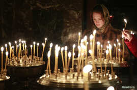 FILE - A woman lights a candle during a religious service at a church in Kyiv, February 23, 2014.