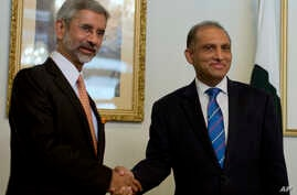 Indian Foreign Secretary Subrahmanyan Jaishankar, left, poses for photographers, as he shakes hands with his Pakistani counterpart Aizaz Chaudhry at the foreign ministry in Islamabad, Pakistan, Tuesday, March 3, 2015.