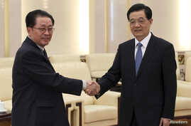 China's President Hu Jintao (R) shakes hands with Jang Song Thaek, Chief of the Central Administrative Department of the Workers' Party of Korea, in Beijing, August 17, 2012.