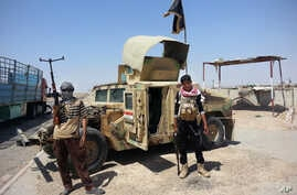 Al-Qaeda inspired militants stand with captured Iraqi Army Humvee at a checkpoint outside Beiji refinery, north of Baghdad, Iraq, June 19, 2014.