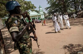 FILE - A Burundian member of the peacekeeping force from the U.N. Multidimensional Integrated Stabilization Mission in the Central African Republic (MINUSCA) stands guard as Muslims leave the Grand Mosque in the PK5 neighborhood of Bangui, Nov. 27, 2