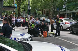 Members of the public watch as police and emergency services attend to an injured person after a car hit pedestrians in central Melbourne, Australia, Jan. 20, 2017.