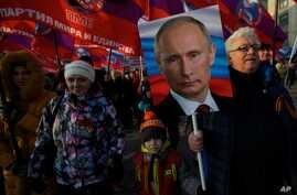 Pro-government activists with Russian flags carry a portrait of President Vladimir Putin marching through downtown Moscow to mark People's Unity Day, Nov. 4, 2014.