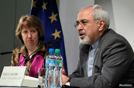 EU foreign policy chief Catherine Ashton listens as Iranian Foreign Minister Mohammad Javad Zarif (R) speaks during a news conference at the end of the Iranian nuclear talks in Geneva, Switzerland, Nov. 10, 2013.