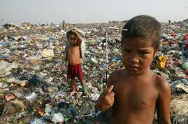Children scavengers pose with their metal hooks used to rummage garbage amidst a mountain of garbage in a Manila dumpsite. (File Photo)