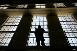 A guard stands watch over the east block of death row at San Quentin State Prison, Aug. 16, 2016, in San Quentin, Calif.