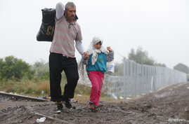 Migrants walk along a railway track as they cross the Hungarian border with Serbia near a collection point in Roszke, Hungary, Sept. 11, 2015.
