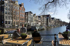 FILE - Men enjoy the afternoon sun at the Brouwersgracht canal in Amsterdam, April 2, 2013.