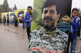 Lebanon's Hezbollah boy scouts carry a picture of Hezbollah commander Hassan al-Laqis during his funeral in Baalbeck, in Lebanon's Bekaa valley, Dec. 4, 2013.