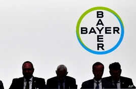 FILE - Members of the supervisory board  sit in front of the company logo during the annual shareholders meeting of German chemical giant Bayer AG in Bonn, Germany, May 25, 2018.