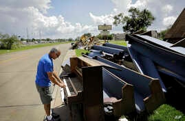 Wayne Christopher plays the keys on a piano put out on the curb in Port Arthur, Texas, Sept. 25, 2017, next to pews from the Memorial Baptist Church which he'd attended his whole life.