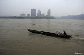 A fisherman drives his boat upstream at the junction of the Min and Dadu Rivers near the city of Leshan, Sichuan province July 22, 2009.