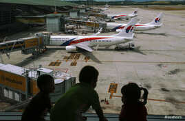 FILE - Children look at Malaysia Airlines Boeing 737-800 aircrafts parked at Kuala Lumpur International Airport, June 14, 2014.