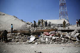 Policemen gather at the site of a Saudi-led airstrike on the police headquarters in Sana'a, Yemen, Jan. 18, 2016.