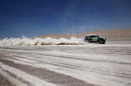 FILE - Driver Stephane Peterhansel and co-driver Jean Paul Cottret, both from France, compete in the 13th stage of the 2012 Argentina-Chile-Peru Dakar Rally between Nazca and Pisco, Peru, Jan. 14, 2012.