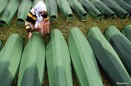 A Bosnian woman cries beside the coffin of a relative at the Potocari Memorial Center, near Srebrenica, July 11, 2013.