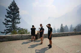 Hein and Teijs Reijnders try to see through the smoke at the famous Tunnel View vista in Yosemite National Park during its reopening day in California, Aug. 14, 2018.
