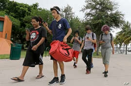 A group of Pokemon Go players check their smartphones as they look for Pokemon, Tuesday, July 12, 2016, at Bayfront Park in downtown Miami.