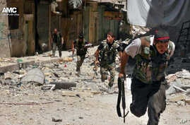 This Tuesday, July 9, 2013 citizen journalism image provided by Aleppo Media Center AMC, which has been authenticated based on its contents and other AP reporting, shows Syrian rebels running during heavy clashes with Syrian soldiers loyal to Syrian