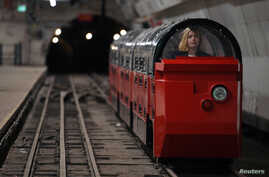 A museum worker sits in a battery-powered train on the Mail Rail tracks of the Mount Pleasant Sorting Office underground station in London, Britain, Aug. 7, 2017.