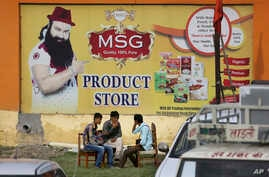 People sit outside the store belonging to Dera Sacha Sauda sect chief Gurmeet Ram Rahim Singh after it was closed down by authorities near Sonipat, India, Aug. 26, 2017.