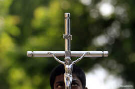An altar boy looks up at a crucifix he is holding during a special Good Friday mass at a church in Colombo, April 18, 2014.