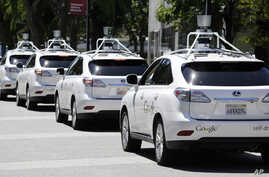 FILE - This May 13, 2014, file photo shows a row of Google self-driving Lexus cars at a Google event outside the Computer History Museum in Mountain View, Calif.
