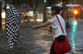 A woman struggles an umbrella in strong winds and rain caused by Typhoon Halong in Tokyo, Japan, Aug. 10, 2014. T