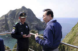 South Korean President Lee Myung-bak, right, talks with police officer Yoon Jang-soo as Lee visits islands called Dokdo in Korea and Takeshima in Japan, Aug. 10, 2012.