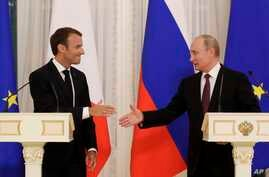 Russian President Vladimir Putin (R) and French President Emmanuel Macron, shake hands after their joint news conference following the talks at the Konstantin palace with the statue of the Peter The Great in the background just outside St. Petersburg