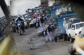 FILE - A reflection from the wing mirror of a car shows people ride motorcycles in Douala.