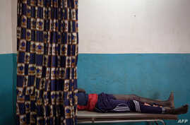FILE - A young man wounded by gunshot is treated at Paoua's hospital, northwestern Central African Republic, Dec. 28, 2017.