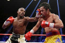 Floyd Mayweather Jr., left, hits Manny Pacquiao, from the Philippines, during their welterweight title fight in Las Vegas, Nevada, May 2, 2015.