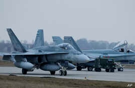 File - In this Nov. 19, 2014, photo, a Canada CF-188 Hornet jet fighter prepares for take off during NATO drills near Vilnius, Lithuania. Canada announced on June 7, 2017, a plan to increase military spending that includes the purchase of 88 fighter