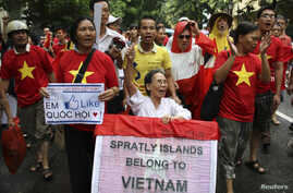 FILE - Anti-corruption activist Le Hien Duc (C) is assisted by anti-China protesters as they march during a protest along a street in Hanoi.