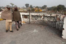 Indian villagers inspect the damage on the roof of a house, caused allegedly by firing from the Pakistan side of the border at Bainglad village in Samba sector, about 52 Kilometers from Jammu, India, Jan. 3, 2015.