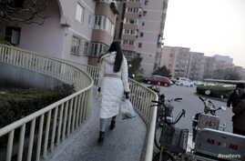 """A women is seen walking toward her apartment building in Beijing, Feb. 10, 2015. An emotional video ad about """"leftover women"""" in China has gone viral, uncovering the society's deep-rooted discrimination against single women."""