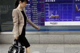 A woman walks by a securities' firm in Tokyo, Friday, Sept. 24, 2010. The Nikkei 225 stock average lost 1.3 percent to 9,446.71 in morning trading as Asian stock markets mostly fell Friday after a jump in U.S. unemployment claims provided more eviden