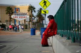 """Ted Payne rests as he works for tips dressed as Elvis at the """"Welcome to Las Vegas"""" sign in Las Vegas, March 3, 2016."""