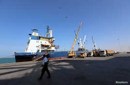 A coast guard walks past a ship docked at the Red Sea port of Hodeida, Yemen, Jan. 5, 2019.