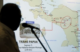 Indonesia's Minister of Public Works and Public Housing Basuki Hadimuljono shows a Papua map during a news conference, Dec. 4, 2018, in Jakarta, Indonesia.