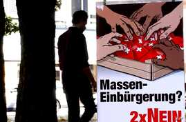 FILE - A man walks by a poster of the Swiss People's Party (SVP/UDC) argueing against the automatic right to citizenship, even for children born in Switzerland to foreign parents on Sept. 9, 2004.