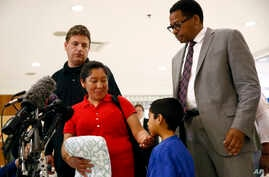 Beata Mariana de Jesus Mejia-Mejia, second from left, rubs her son Darwin Micheal Mejia's chin as she speaks at a news conference following their reunion at Baltimore-Washington International Airport, in Linthicum, Maryland, June 22, 2018.