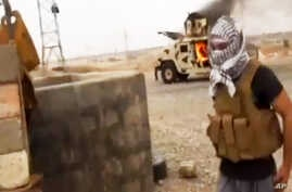 A militant standing in front of a burning Iraqi Army Humvee in Tikrit, Iraq, June 12, 2014.